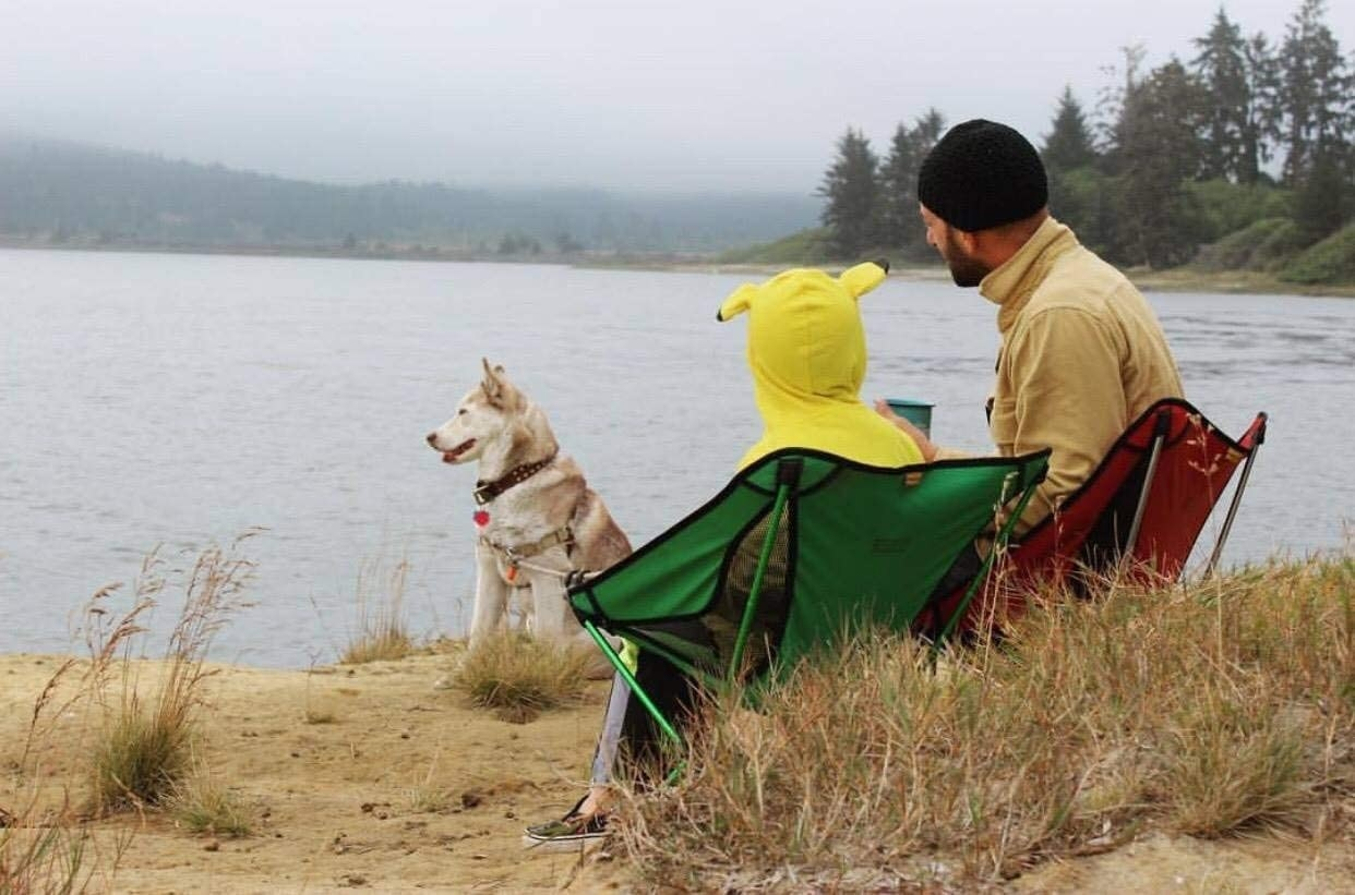 Two people sitting on foldable camping chairs by a dog on a beach