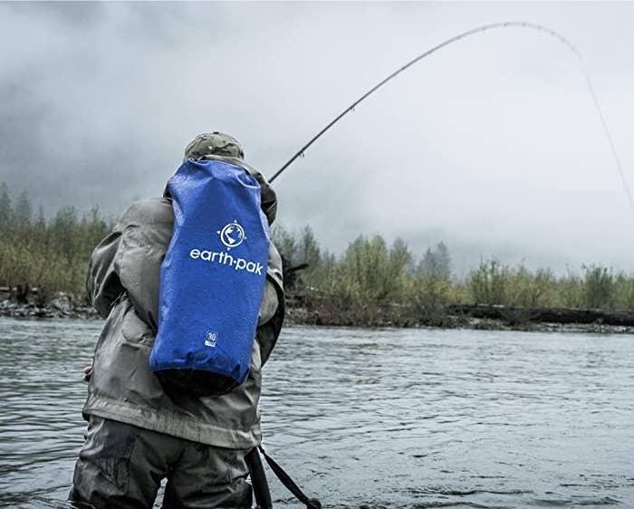 A person fishing with the dry bag on their back