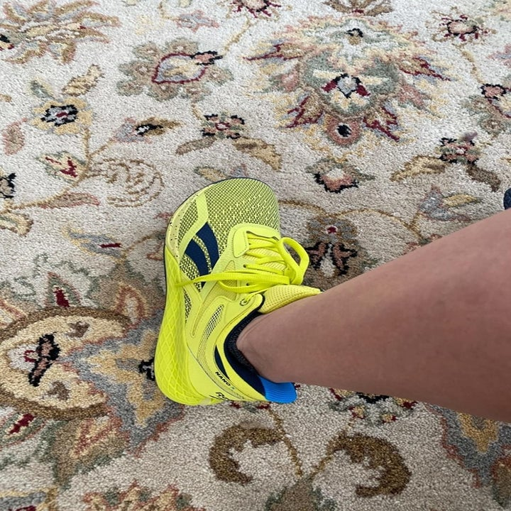 reviewer wears neon yellow cross-training sneaker
