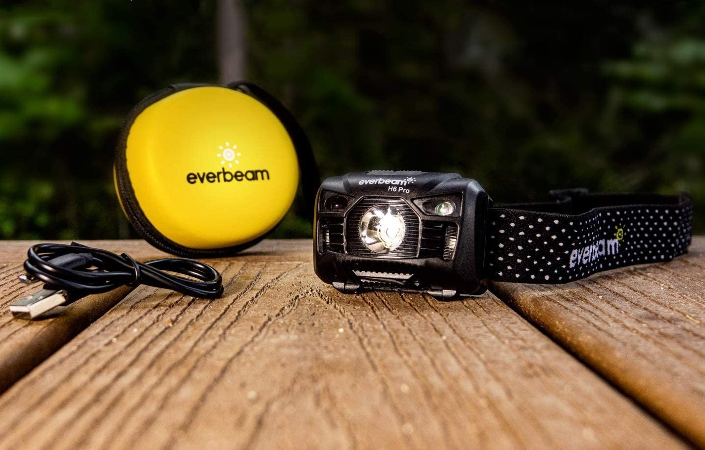 The rechargeable headlamp next to a USB cord and a small, round, protective case