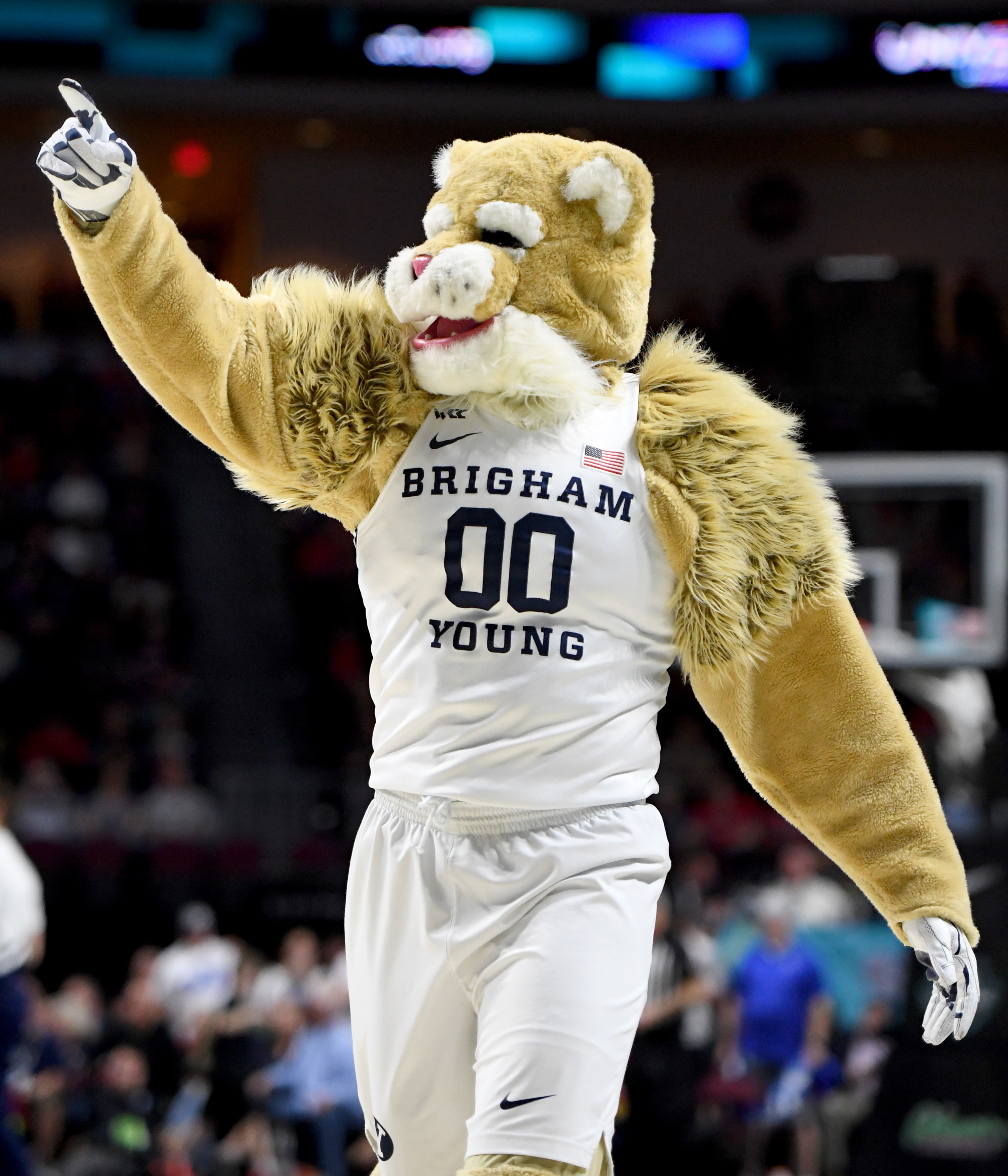 BYU cougar mascot in a white basketball jersey, pointing to the crowd.
