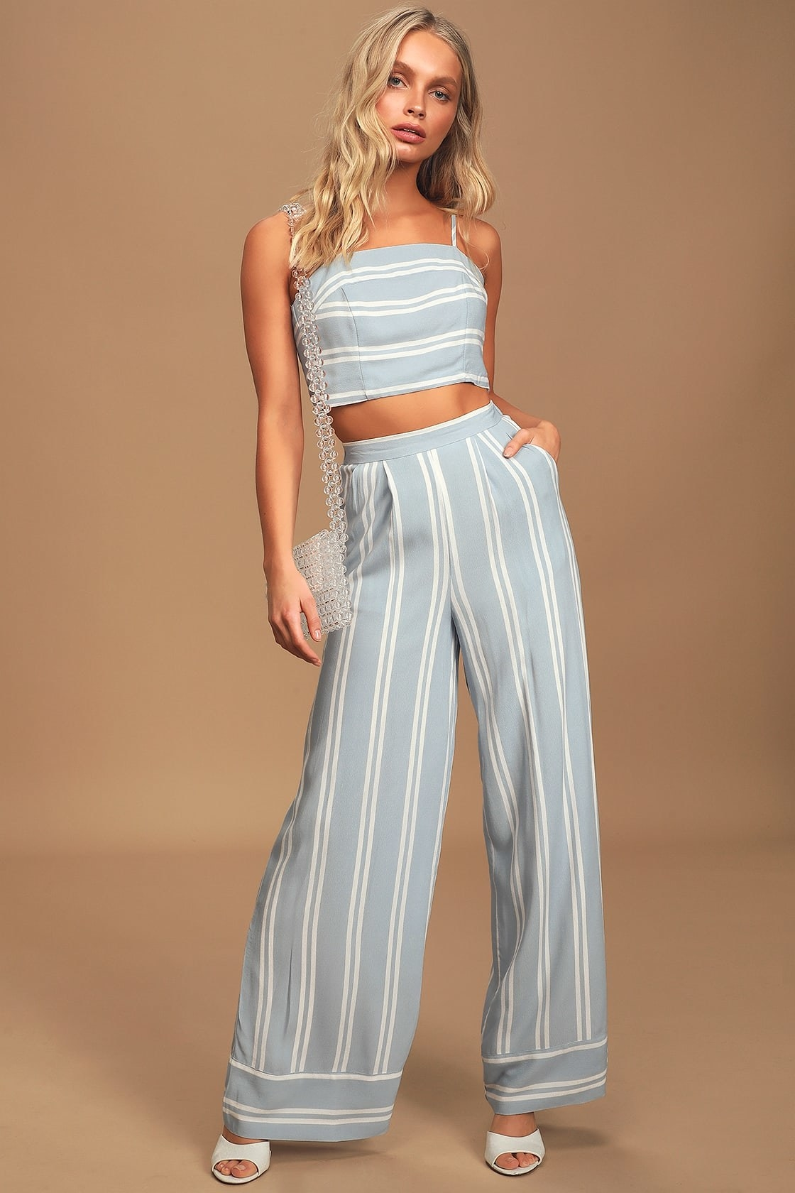 Model wearing the light blue and white strappy tie back top and high-waisted wide leg pants