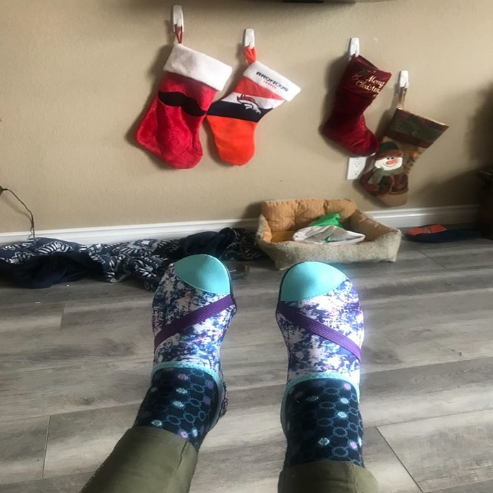 reviewer wears pattered, sock-like FitKick shoes at home