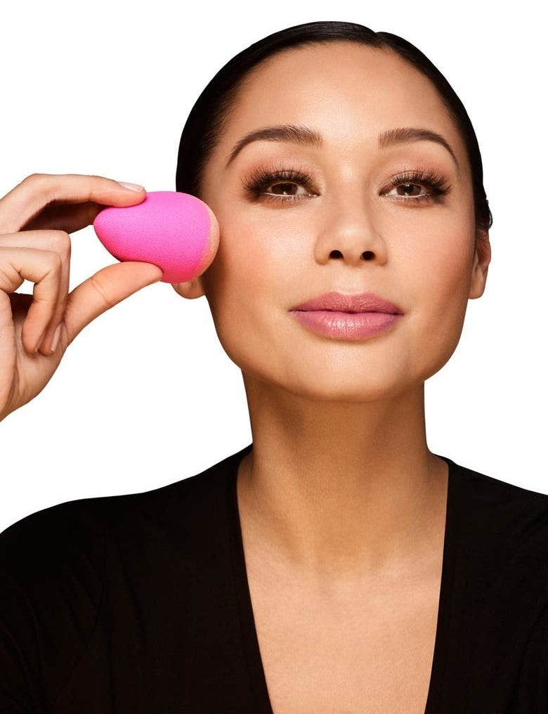 A model uses the sponge to apply cream makeup