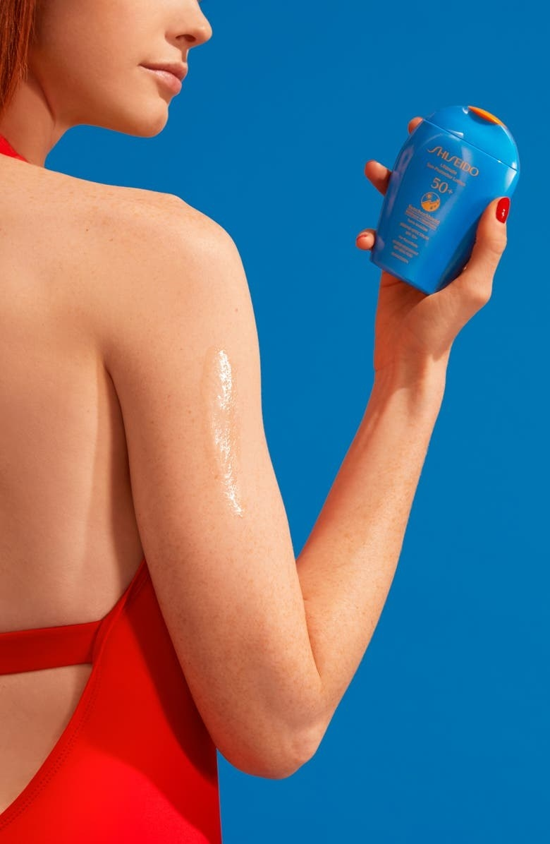 A model holds the sunscreen with a swatch applied to their arm to show its translucency