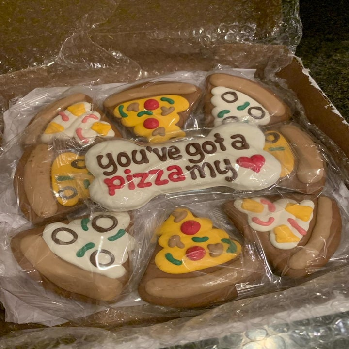 """The cookies, which are decorated to look like slices of pizza with a bone-shaped one in the middle reading """"you've got a pizza my heart"""""""