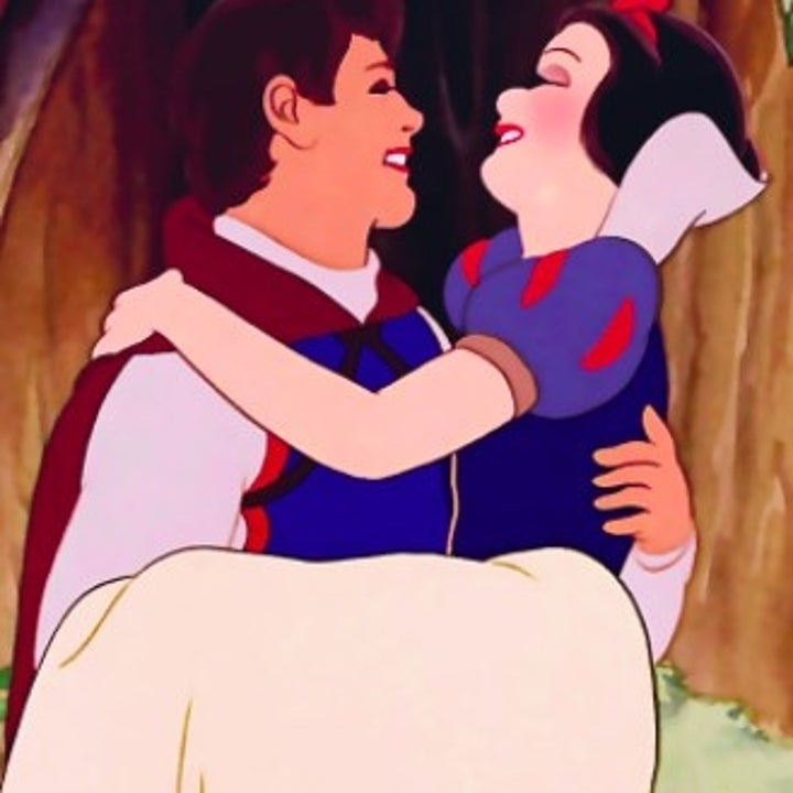 Snow White is carried in the prince's arms while looking at him and smiling