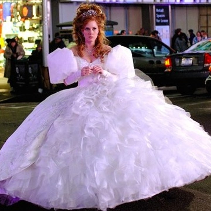 A live action Giselle stands in the street in a huge puffy dress