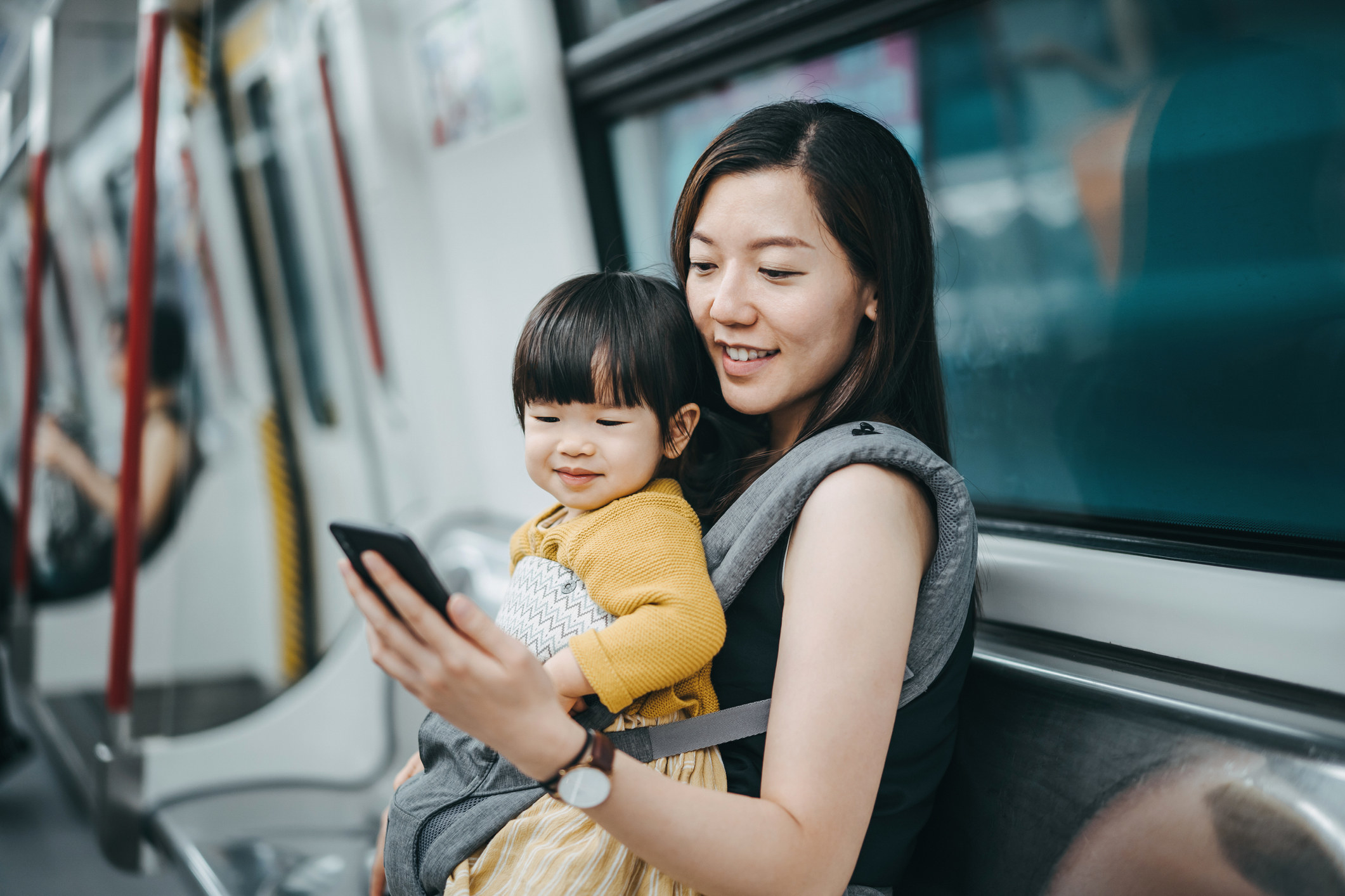 Young mother with cute little daughter using and looking at smartphone with joy while riding on subway