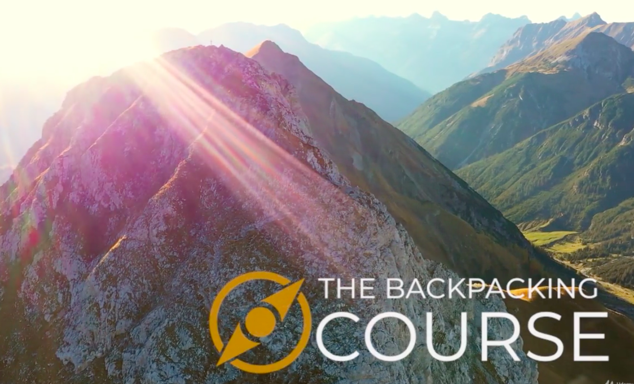 A mountainous range in the sunshine with the words the backpacking course written across it
