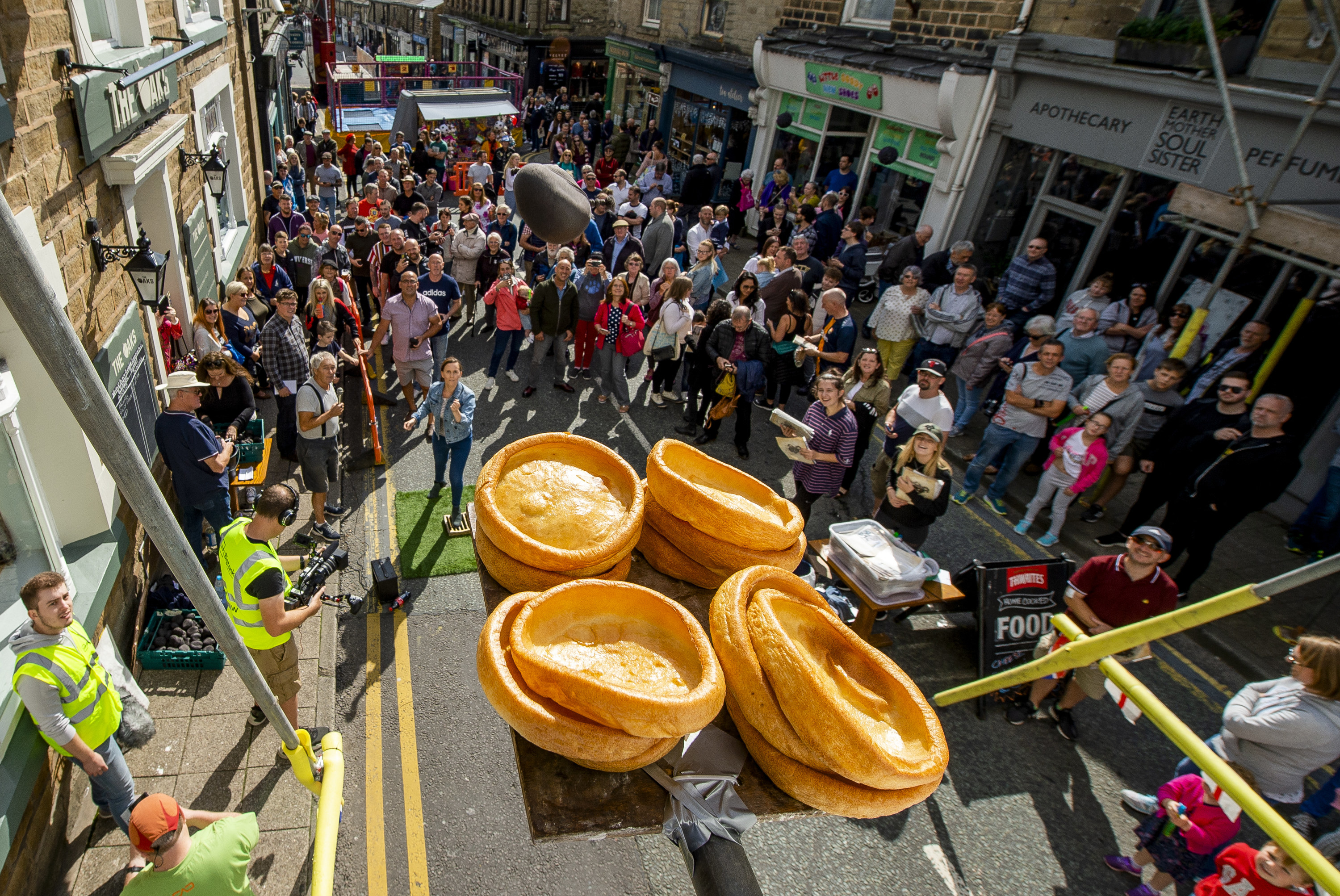 Four Yorkshire puddings on a scaffold with a crowd below throwing black pudding at them