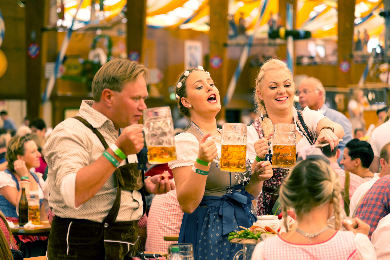 Two women and man drink beer in lederhosen