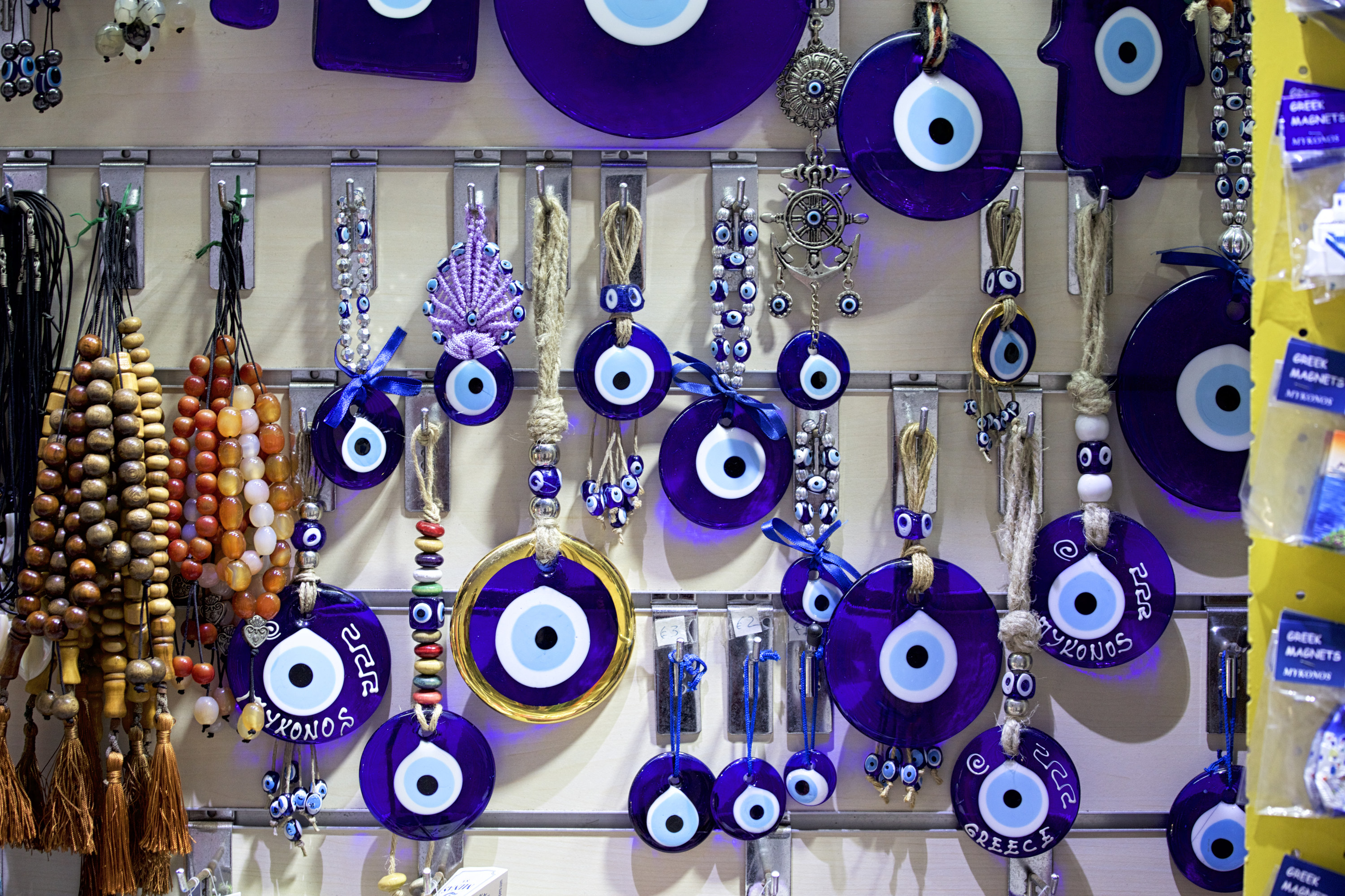 A bunch of evil eye amulets hanging on a wall