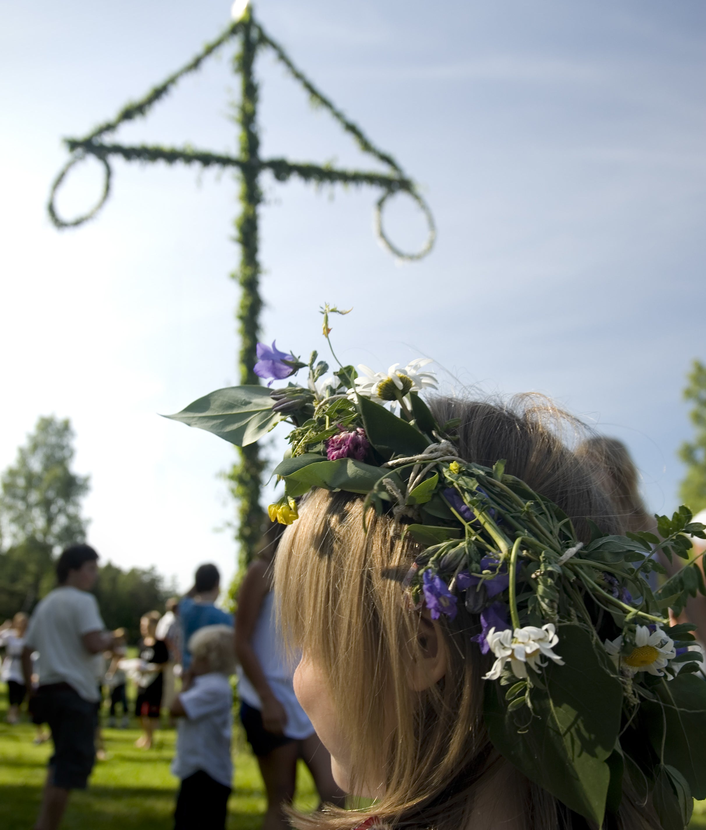 The back of a girl's head, showing her flower crown, with a maypole in the background