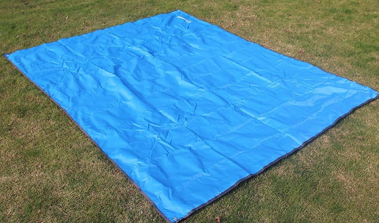 A tarp laid out on some grass