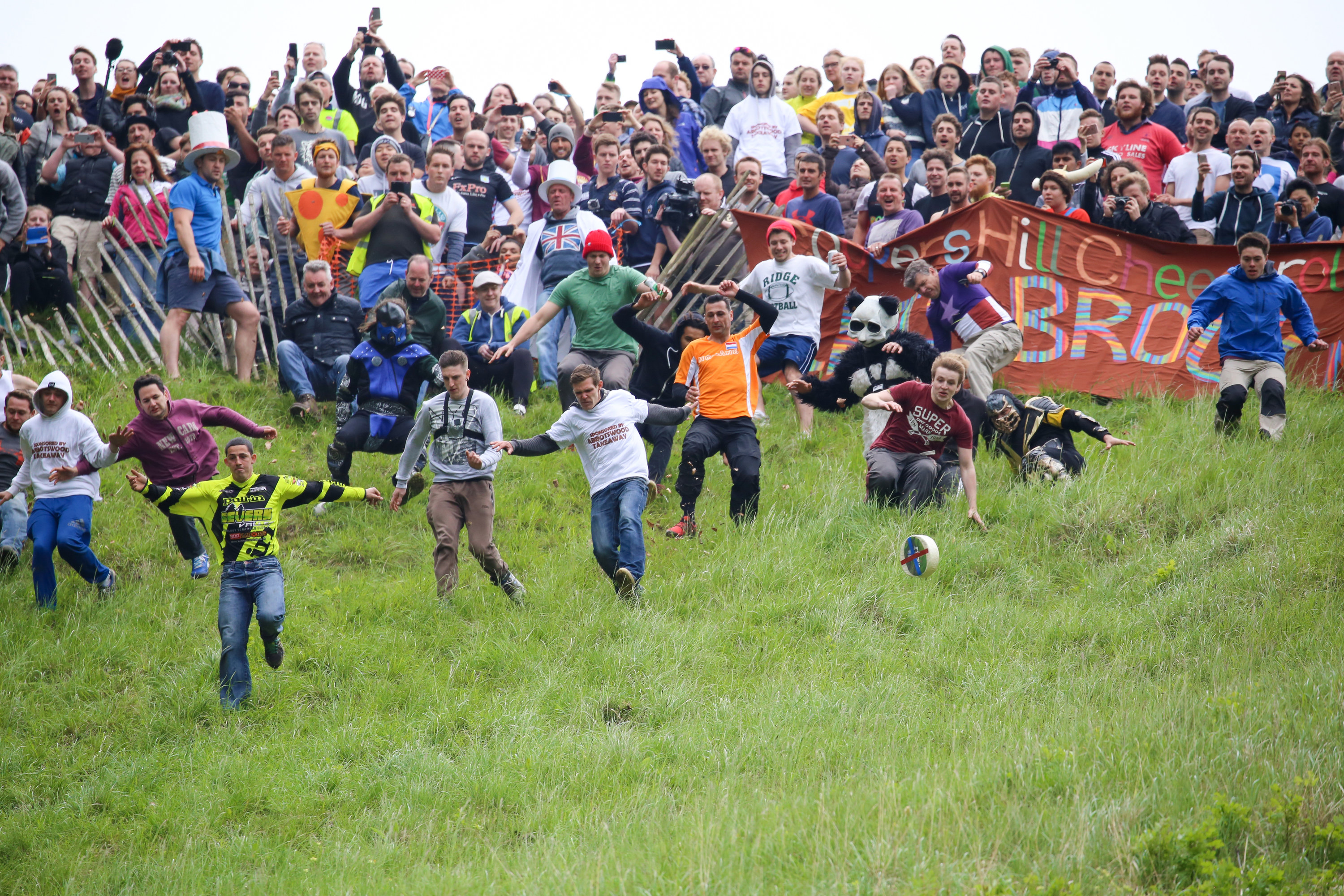 A bunch of people running and stumbling over each other as they chase a round of cheese down a grassy hill