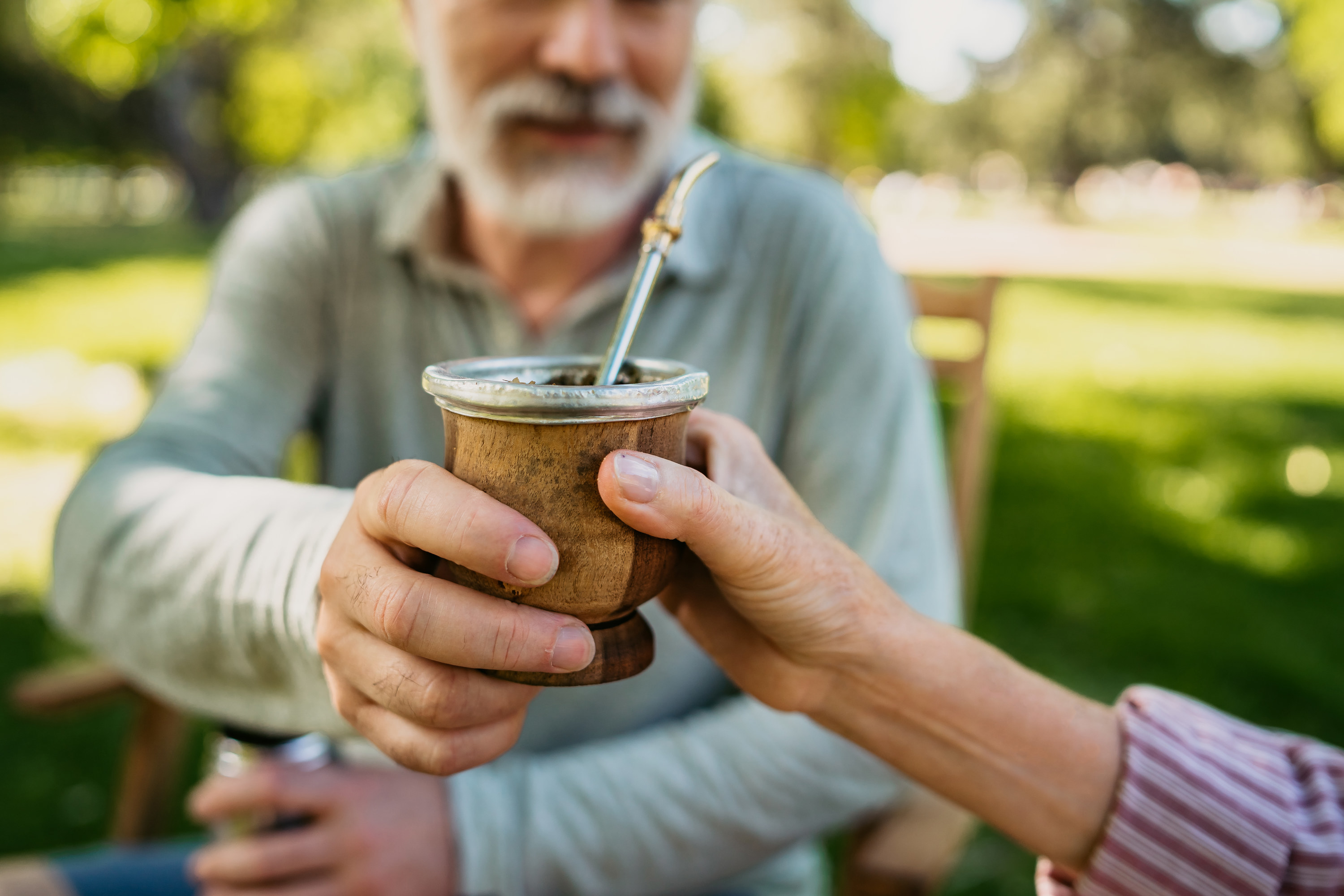 Two people pass a cup of Yerba mate with a metal straw in the cup