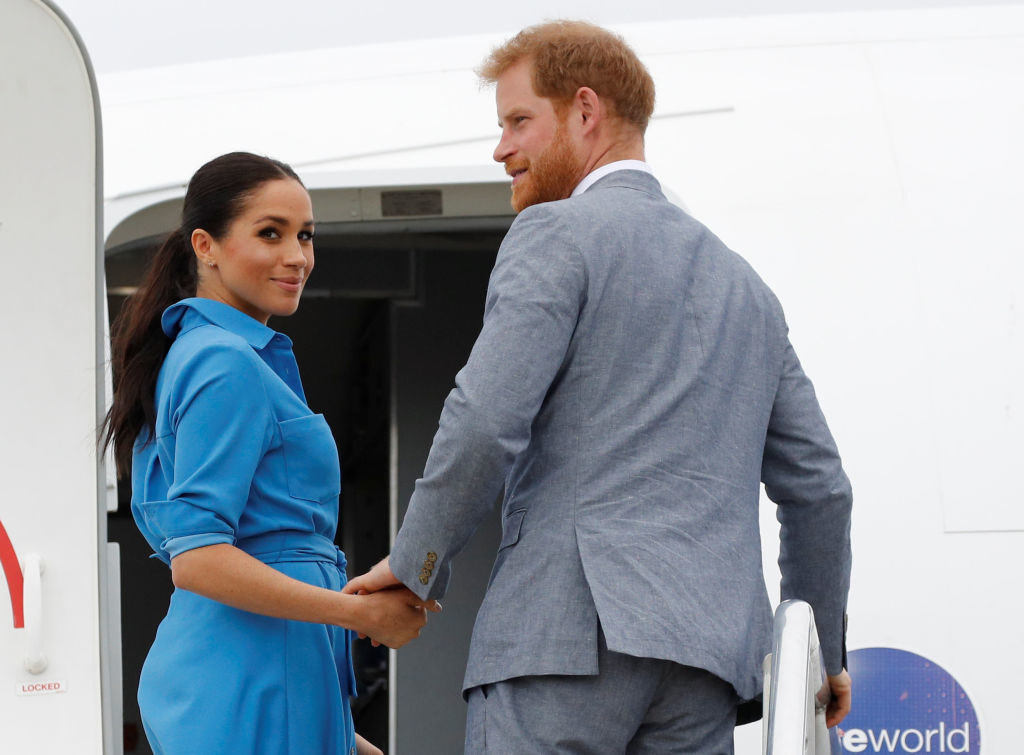 Prince Harry and Meghan look behind them as they board an airplane