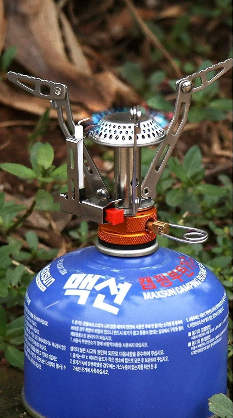 The mini stove attached to a canister of propane