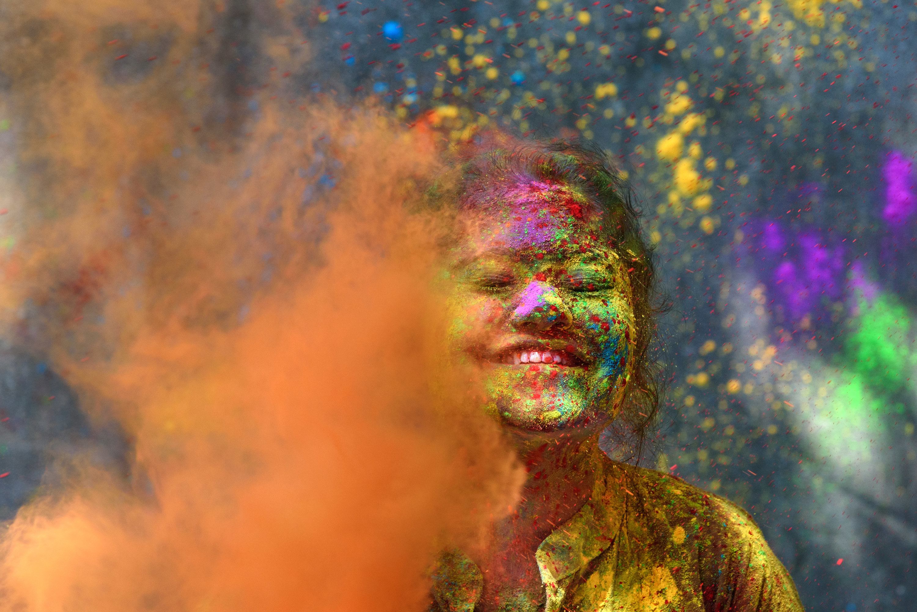 A woman smiling and covered in colors with more being thrown around her on Holi