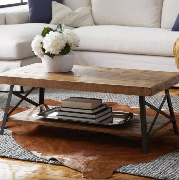 The coffee table with storage in natural pine brown with a vase of flowers on top