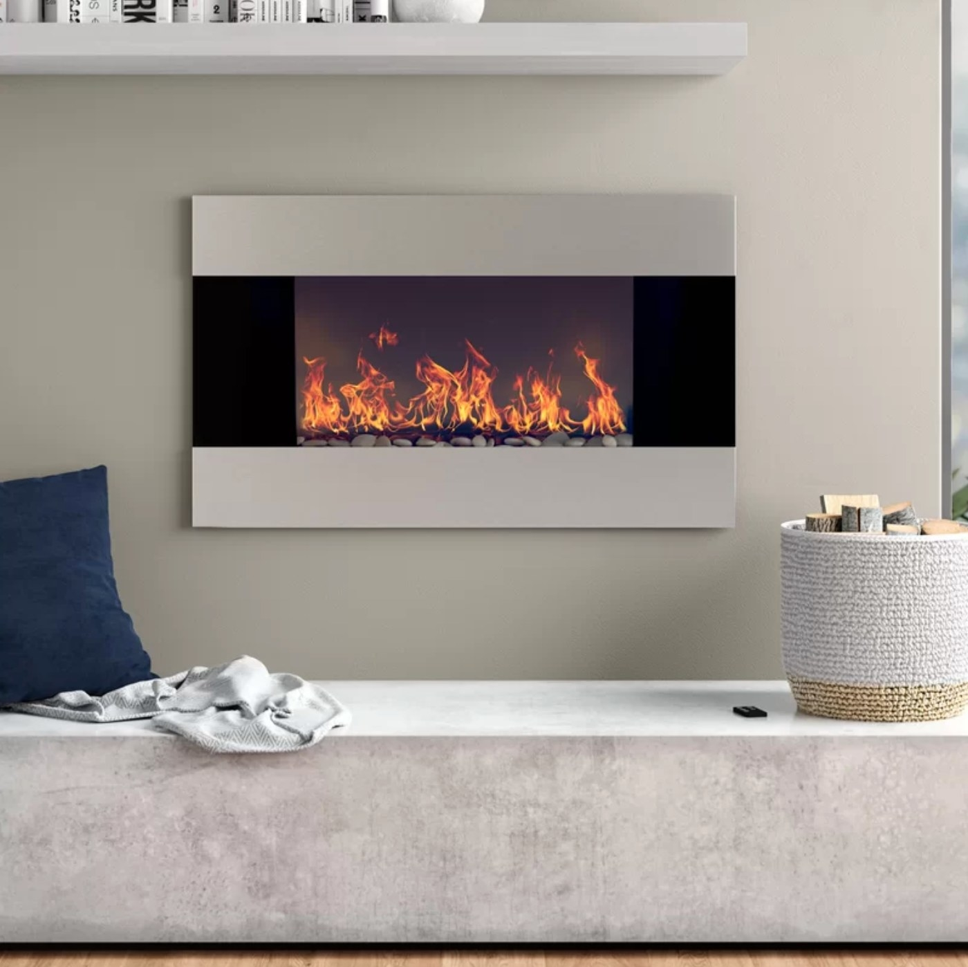 The electric mounted wall fireplace above a gray fabric bench