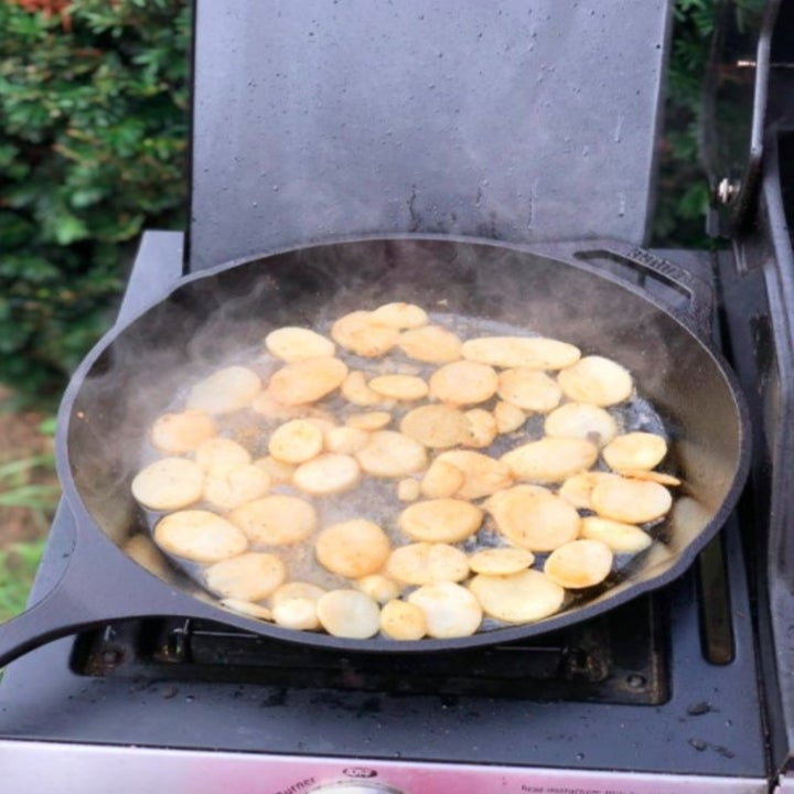 a cast iron skillet cooking potatoes on a grill