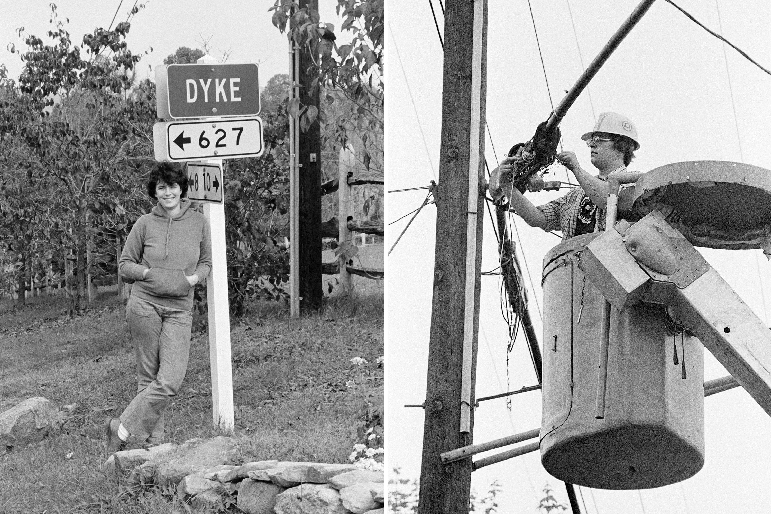 A woman stands in front of a sign saying Dyke and another woman works in a cherrypicker on some power lines