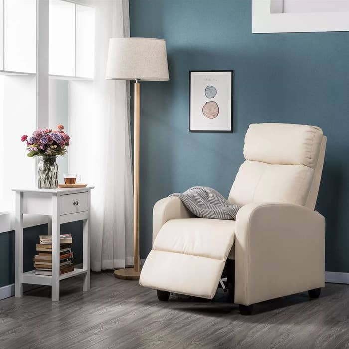 The home theatre individual seat in beige next to a tall floor lamp