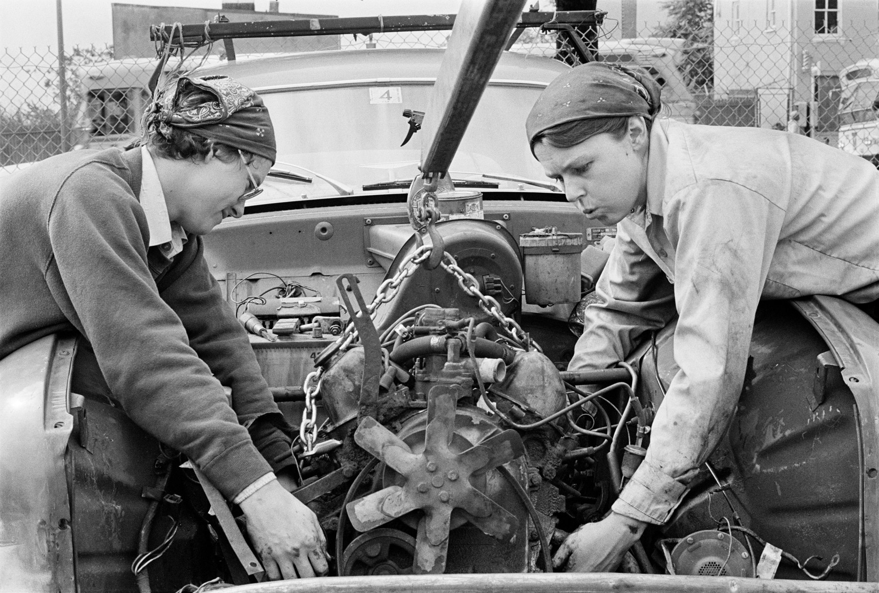 Two women work on a car engine