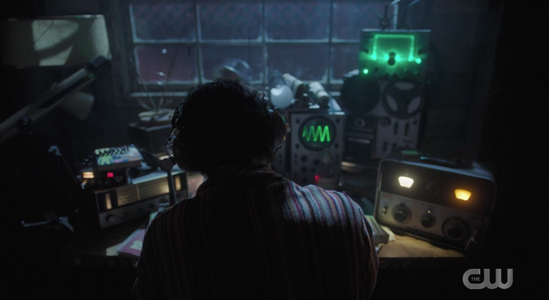 Jughead sitting in his room with tech equipment