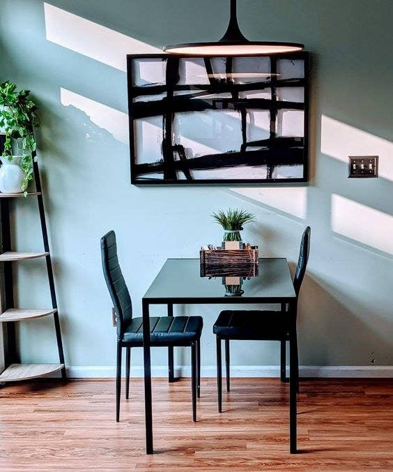 Reviewer's picture of the black sleek dining room table and matching chairs