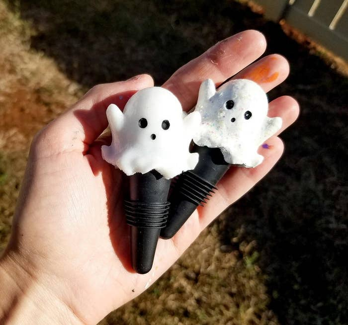 hand holding the ghost bottle stoppers
