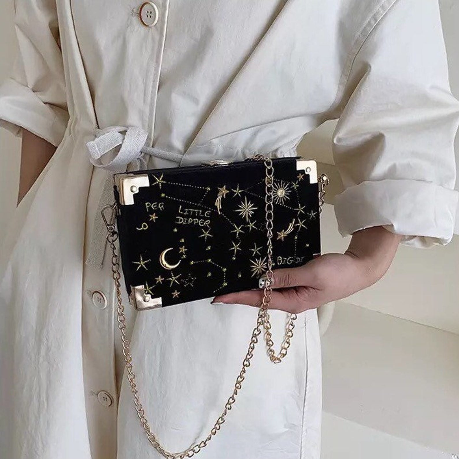 model holding the black purse with gold chain