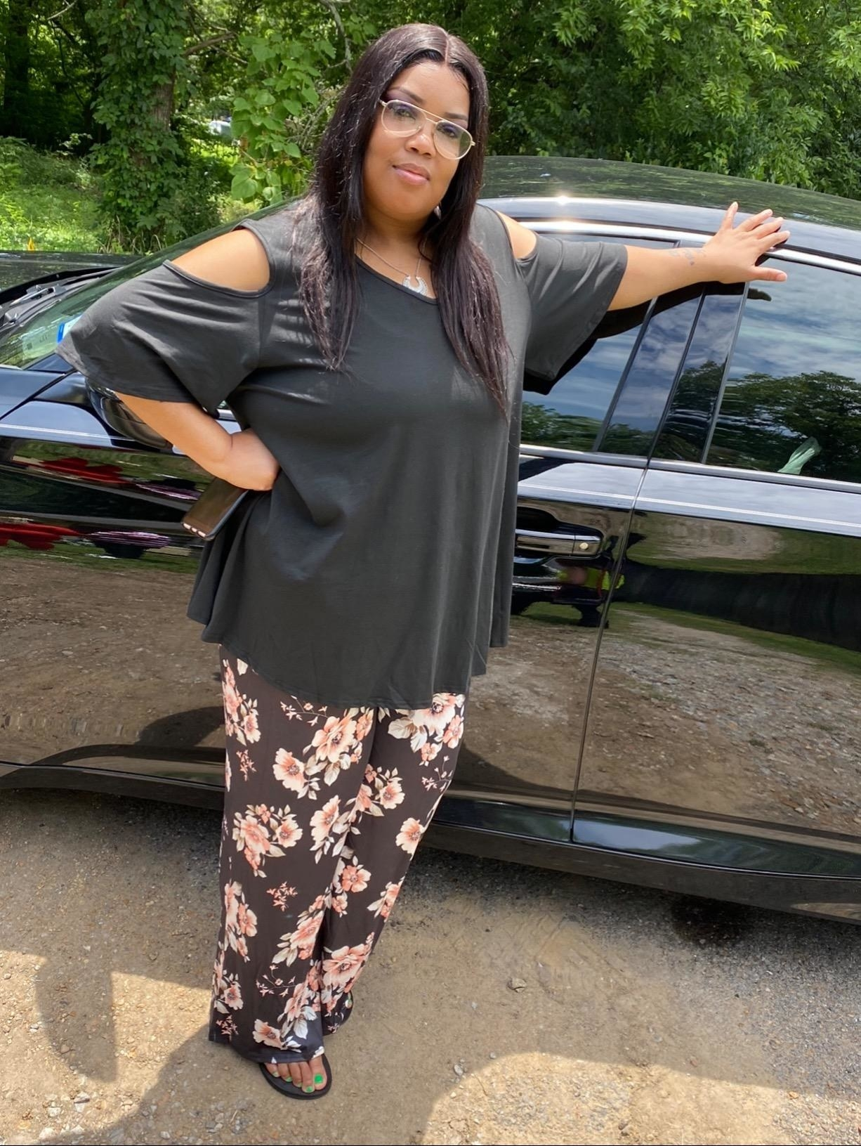 a plus size reviewer wearing the black allegrace cold shoulder top with floral plants