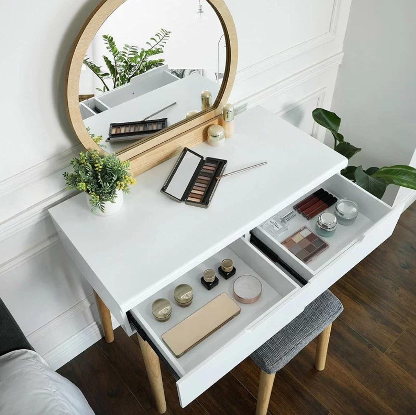 The vanity set with a stool in natural/white holding makeup
