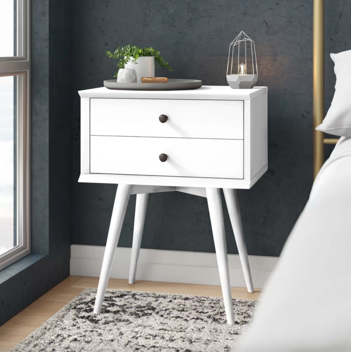 The two drawer solid wood nightstand in white holding a plant and light