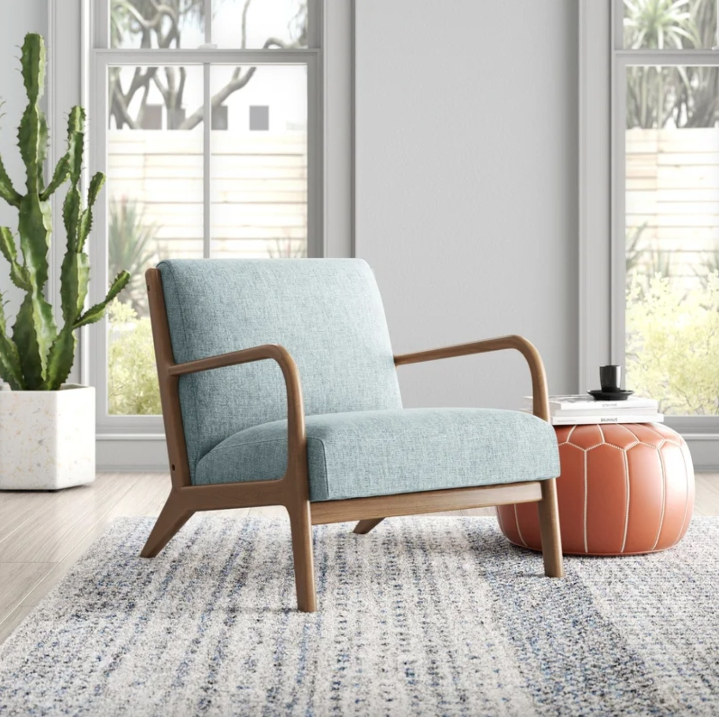 The chair in light blue next to a pouf with books on it