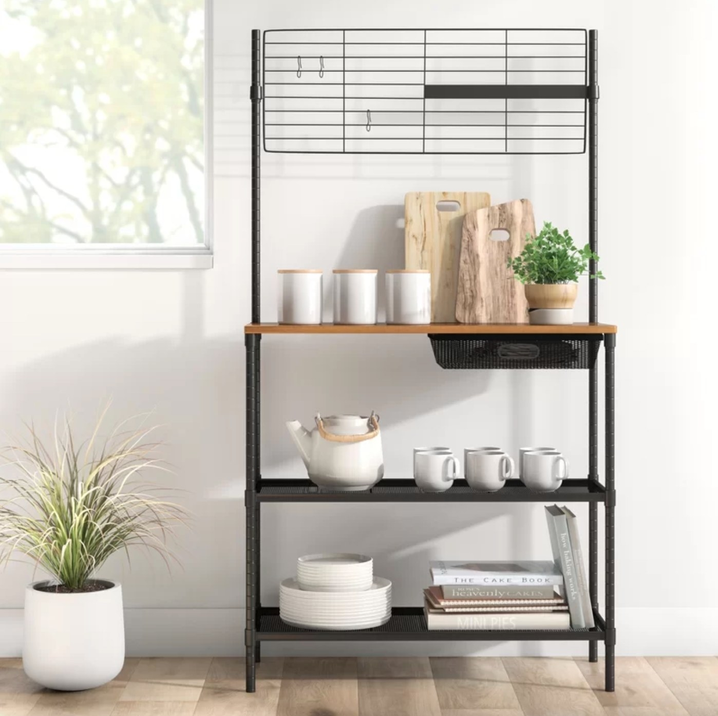 The steel baker's rack holding mugs and cutting boards
