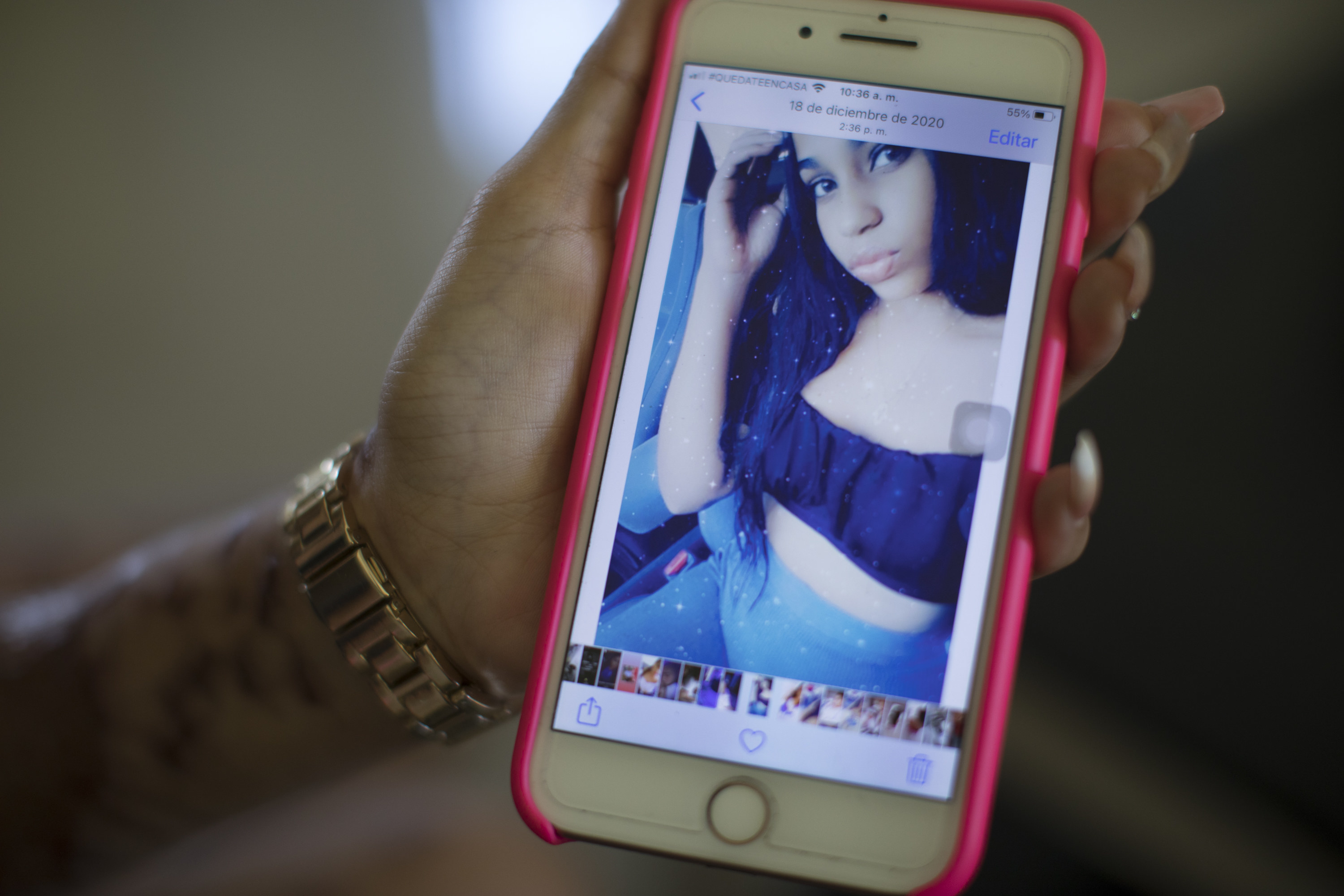 A hand holds up an iPhone, showing a young woman's selfie on the screen
