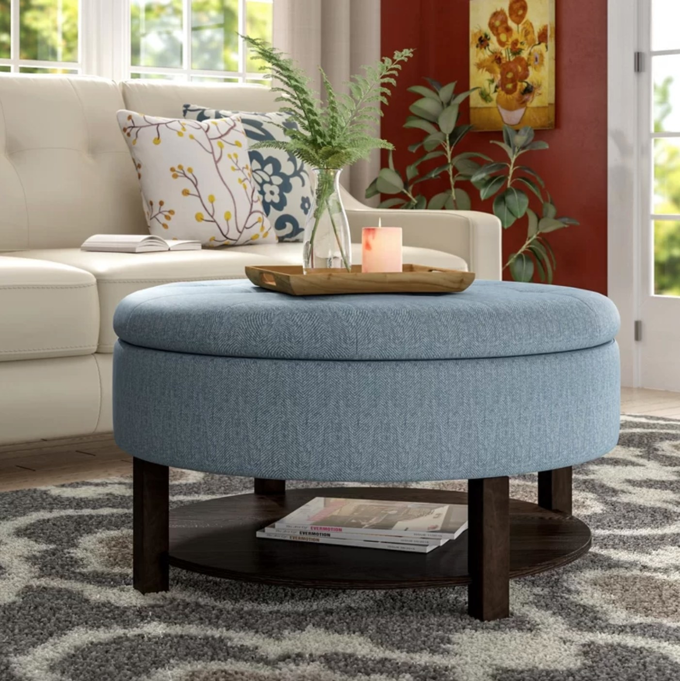 The round storage ottoman in blue with wood legs and an extra storage base with magazines