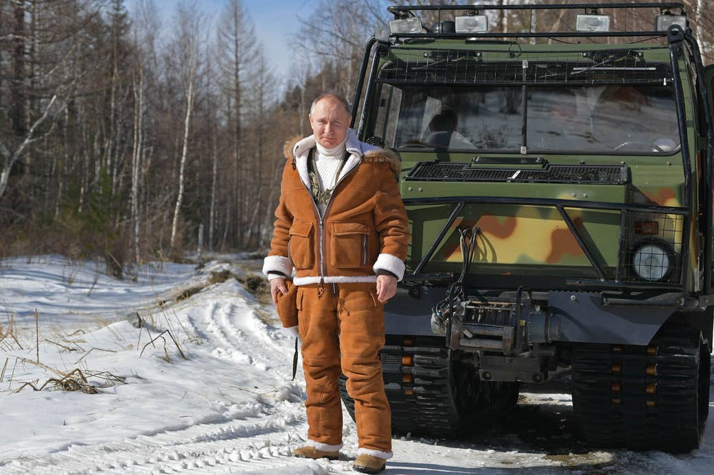 Vladimir Putin by an all-terrain vehicle in a forest, dressed in a sweatsuit