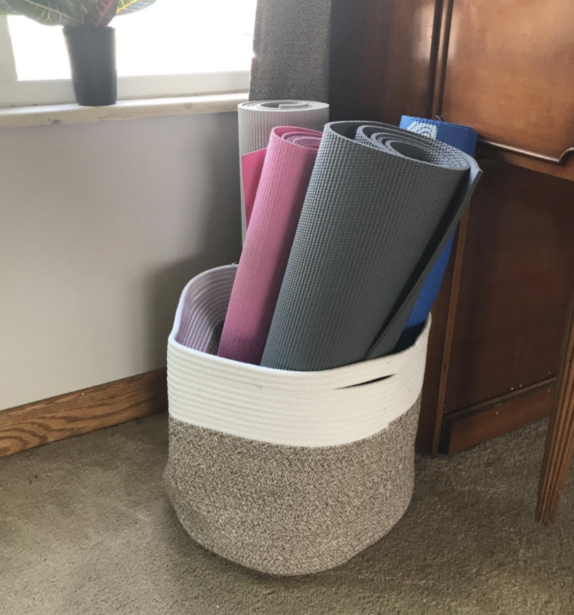 A reviewer's basket being used to store yoga mats