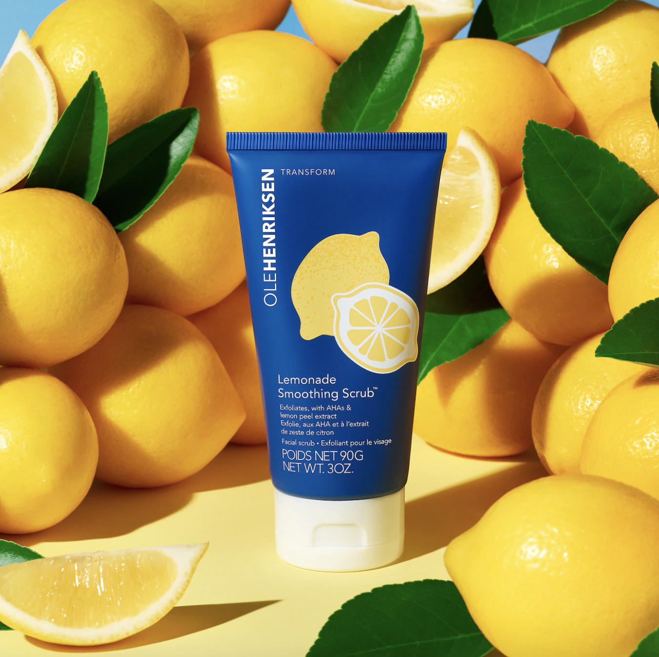 the blue bottle of scrub next to a bunch of lemons