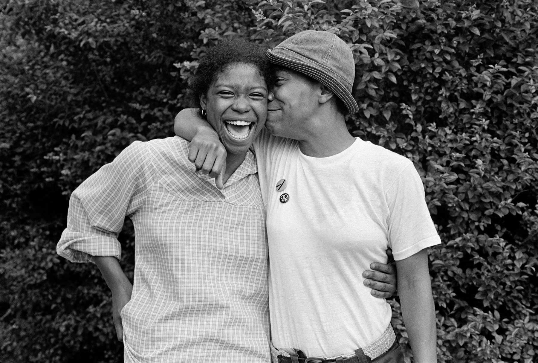 Two Black women smiling and embracing, wearing 1970s clothing