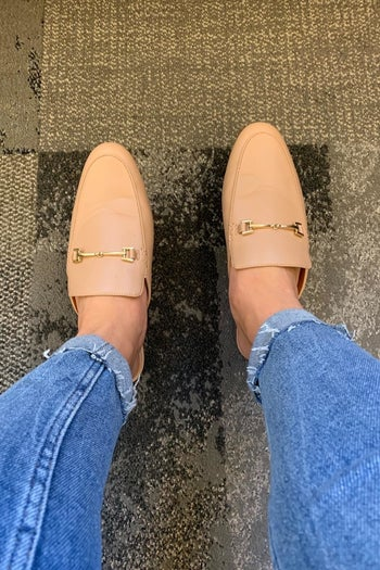 reviewer wearing the buckle-detail loafer mules in tan