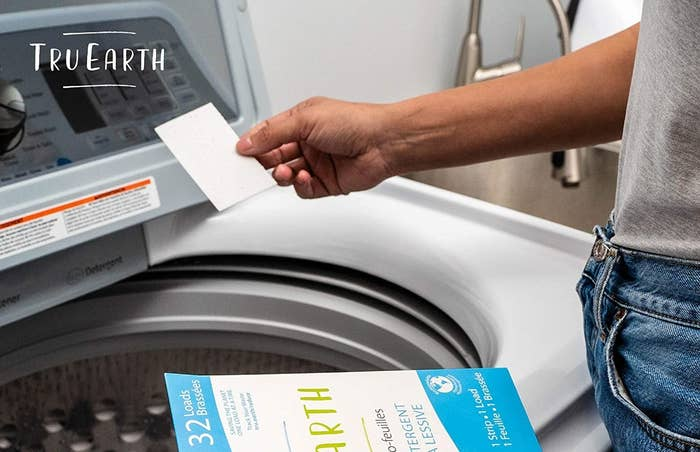 person placing a strip into the washing machine