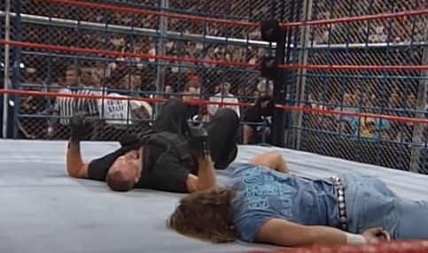 Two men lying down inside a cage.
