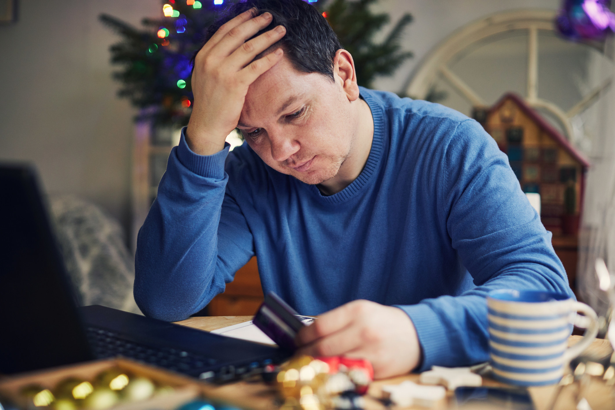 a stressed out man holiday shopping online