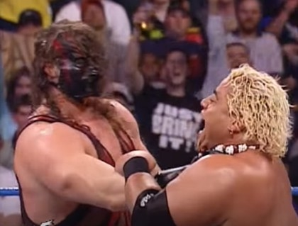 Masked wrestler Kane choking opponent.
